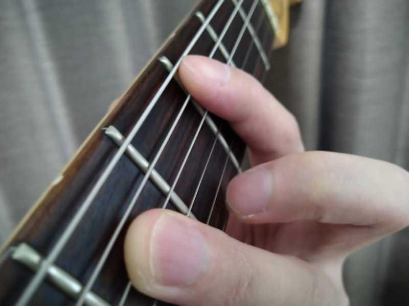左手の人差し指で6弦を軽く触れてミュートをしている状態