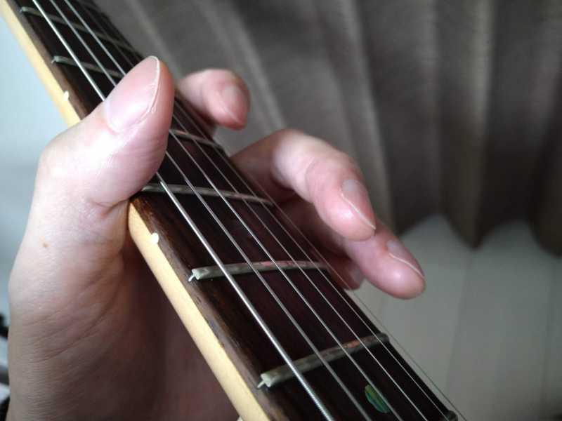 「人差し指の付け根の側面」をネックの下部に固定して支点を作る