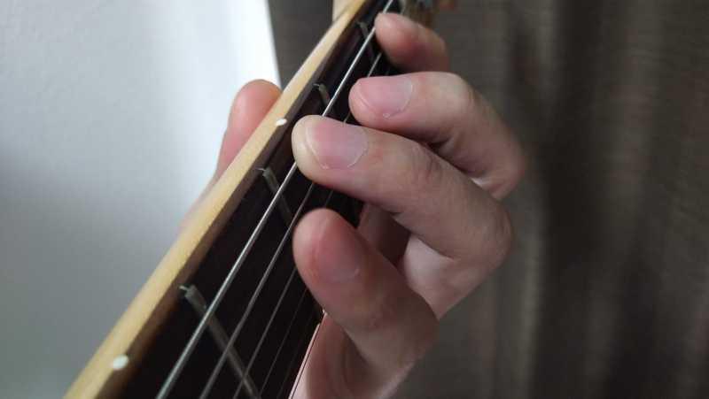 薬指がいつでも押さえられる状態で右手のピッキングに合わせて押弦している状態