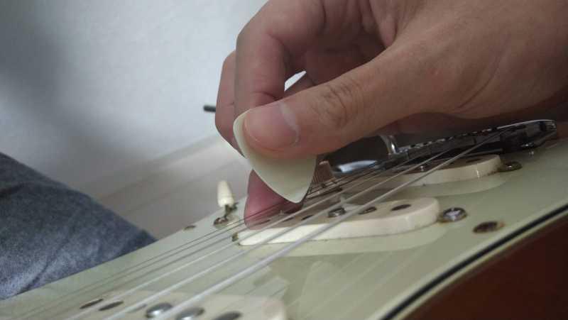 小指や薬指をピックガードに固定して1弦をピッキングしたフォーム