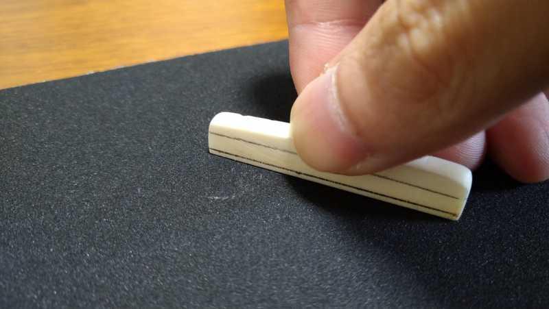 ブリッジのサドルを粗削り用の紙やすりで削る