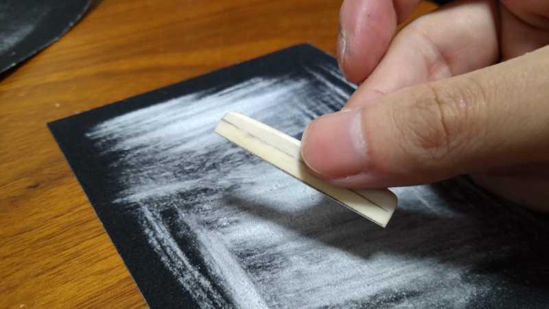 ブリッジのサドルを粗削り用の紙やすりで削り終わった後