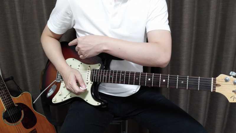エレキギターの右手の二の腕をボディーに軽く載せる構え方を正面からみた場合