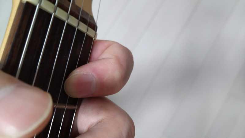 左手の人差し指の付け根側面をネック下部に添える