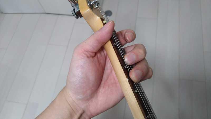 左手の人差し指の付け根側面をネック下部にそえる