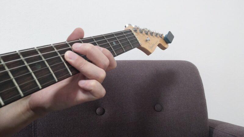 第一関節を少し反らして3弦7フレットを押弦し、5弦はフレットから浮いていますが、指先で軽く触れている状態にしてミュート