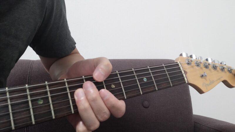 左手全体を前後させて弦を弾き分けようとしてしまうと、左手の形が崩れてしまう悪い例