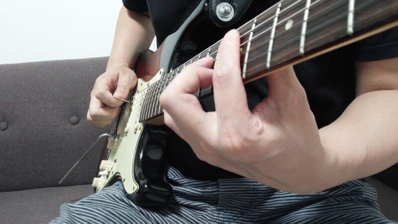 弦を指で引っ張り離す