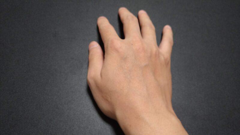 机の上に自然に手を置き、親指で机をさするように動かす感覚